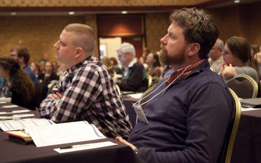 Two people listening at wetland science conference