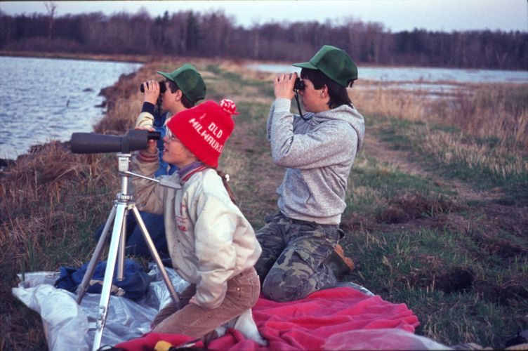 Group of people looking into wetland with binoculars in late winter