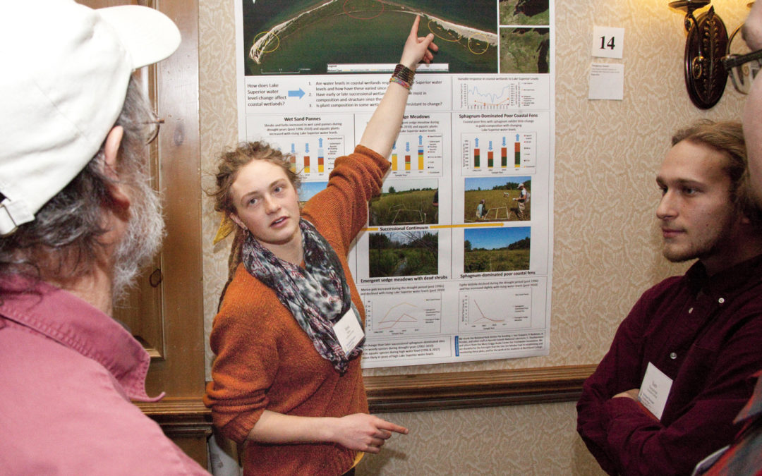 A student poster presenter explains her poster to fellow Wetland Science Conference attendees.