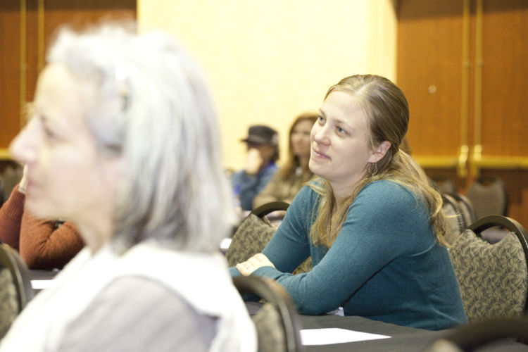 A conference attendee listens happily to a presentation.