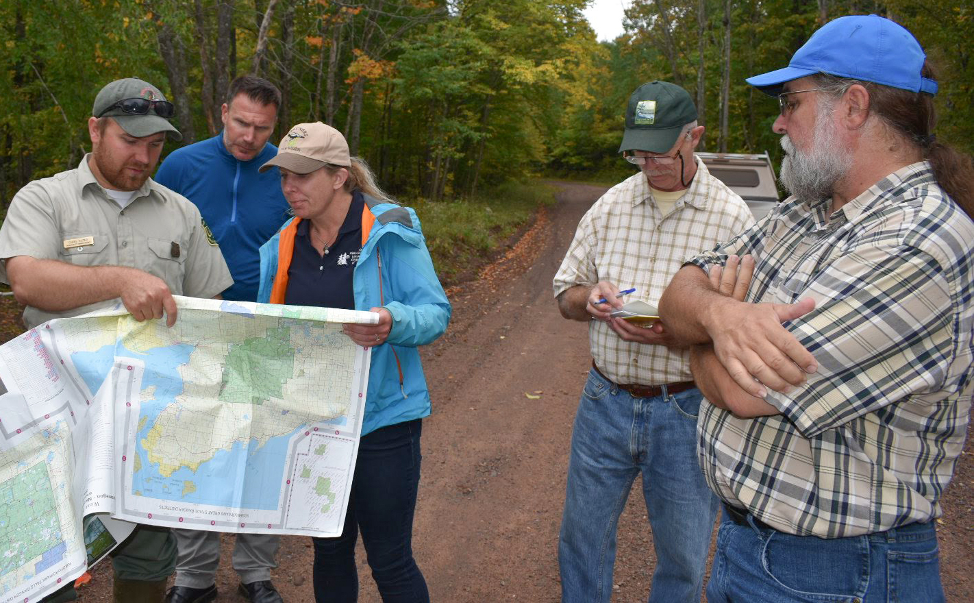 People gathered around a map in a natural area, with WWA's Tracy Hames in the foreground.
